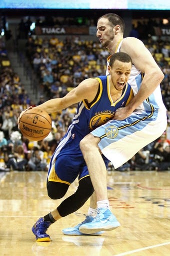 Apr 30, 2013; Denver, CO, USA; Denver Nuggets center Kosta Koufos (41) fouls Golden State Warriors point guard Stephen Curry (30) in the first quarter in game five of the first round of the 2013 NBA Playoffs at the Pepsi Center. The Nuggets won 107-100. Mandatory Credit: Isaiah J. Downing-USA TODAY Sports