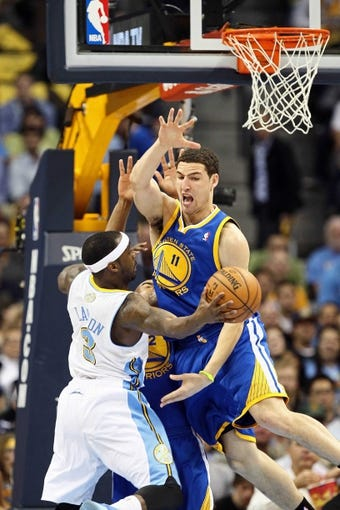 Apr 30, 2013; Denver, CO, USA; Denver Nuggets point guard Ty Lawson (3) passes around the outside of Golden State Warriors shooting guard Klay Thompson (11) in the second quarter in game five of the first round of the 2013 NBA Playoffs at the Pepsi Center. The Nuggets won 107-100. Mandatory Credit: Isaiah J. Downing-USA TODAY Sports
