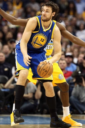 Apr 23, 2013; Denver, CO, USA; Golden State Warriors center Andrew Bogut (12) controls the ball in the fourth quarter against the Denver Nuggets during game two in the first round of the 2013 NBA playoffs at the Pepsi Center. The Warriors won 131-117. Mandatory Credit: Isaiah J. Downing-USA TODAY Sports