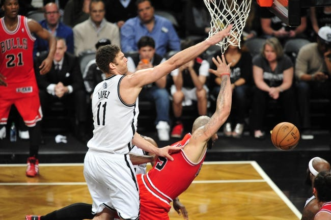 May 4, 2013; Brooklyn, NY, USA; Brooklyn Nets center Brook Lopez (11) fouls Chicago Bulls power forward Carlos Boozer (5) during the second half in game seven of the first round of the 2013 NBA Playoffs at the Barclays Center. The Bulls won 99-93. Mandatory Credit: Joe Camporeale-USA TODAY Sports