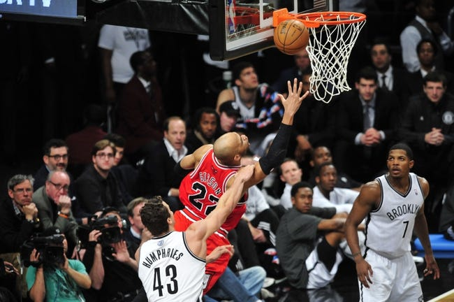 May 4, 2013; Brooklyn, NY, USA; Chicago Bulls power forward Taj Gibson (22) puts up a shot over Brooklyn Nets power forward Kris Humphries (43) during the second half in game seven of the first round of the 2013 NBA Playoffs at the Barclays Center. The Bulls won 99-93. Mandatory Credit: Joe Camporeale-USA TODAY Sports