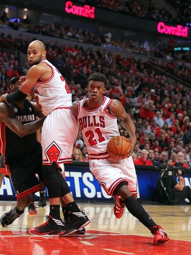 May 10, 2013; Chicago, IL, USA; Chicago Bulls small forward Jimmy Butler (21) drives around a pick set by power forward Taj Gibson (22) on Miami Heat small forward LeBron James (6) during the second half in game three of the second round of the 2013 NBA Playoffs at the United Center. Miami won 104-94. Mandatory Credit: Dennis Wierzbicki-USA TODAY Sports