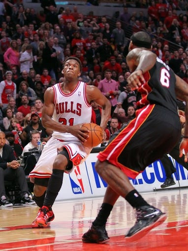 May 10, 2013; Chicago, IL, USA; Chicago Bulls small forward Jimmy Butler (21) drives past Miami Heat small forward LeBron James (6) during the second half in game three of the second round of the 2013 NBA Playoffs at the United Center. Miami won 104-94. Mandatory Credit: Dennis Wierzbicki-USA TODAY Sports