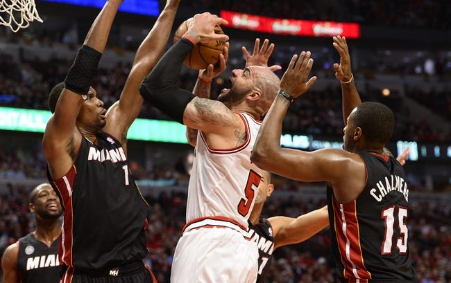 May 13, 2013; Chicago, IL, USA; Chicago Bulls power forward Carlos Boozer (5) shoots the ball against Miami Heat center Chris Bosh (1) and  point guard Mario Chalmers (15) during the second half at the United Center. Miami defeats Chicago 88-65. Mandatory Credit: Mike DiNovo-USA TODAY Sports