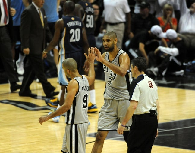 May 21, 2013; San Antonio, TX, USA; San Antonio Spurs forward Tim Duncan (21) and guard Tony Parker (9) react against the Memphis Grizzlies during overtime in game two of the Western Conference finals of the 2013 NBA Playoffs at AT&T Center. San Antonio beat Memphis 93-89. Mandatory Credit: Brendan Maloney-USA TODAY Sports