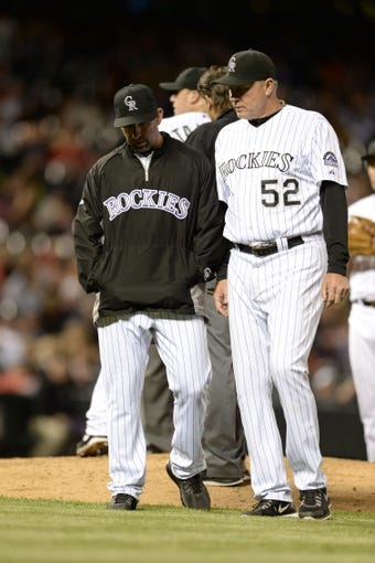 May 21, 2013; Denver, CO, USA; Colorado Rockies manager Walt Weiss (22) and pitching coach Jim Wright (52) talk near the mound during the game against the Arizona Diamondbacks at Coors Field. The Rockies defeated the Diamondback 5-4 in ten innings. Mandatory Credit: Ron Chenoy-USA TODAY Sports