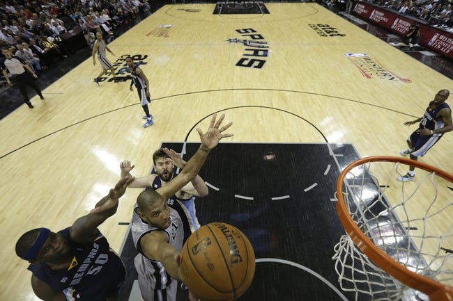 May 21, 2013; San Antonio, TX, USA; San Antonio Spurs forward Tim Duncan (21) drives for the basket between Memphis Grizzlies forward Zach Randolph (50) and center Marc Gasol (behind) in game two of the Western Conference finals of the 2013 NBA Playoffs against the Memphis Grizzlies at AT&T Center. Mandatory Credit: Ronald Martinez/Getty Images-Pool Photo via USA TODAY Sports