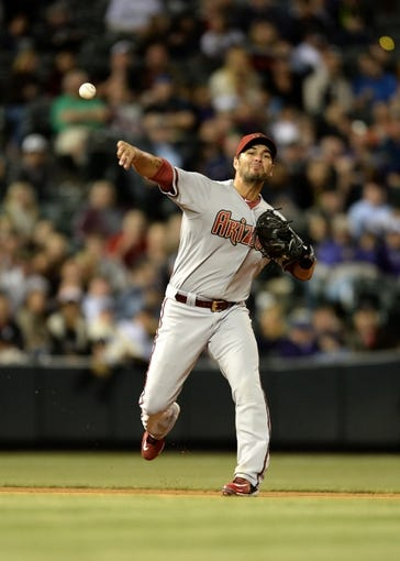 May 21, 2013; Denver, CO, USA; Arizona Diamondbacks third baseman Eric Chavez (12) throws back to first base against the Colorado Rockies at Coors Field. The Rockies defeated the Diamondback 5-4 in ten innings. Mandatory Credit: Ron Chenoy-USA TODAY Sports