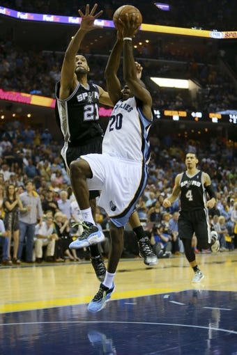 May 25, 2013; Memphis, TN, USA; Memphis Grizzlies small forward Quincy Pondexter (20) goes up for a shot while guarded by San Antonio Spurs power forward Tim Duncan (21) in game three of the Western Conference finals of the 2013 NBA Playoffs at FedEx Forum. San Antonio Spurs defeat the Memphis Grizzlies 104-93, and lead the series 3-0.  Mandatory Credit: Spruce Derden-USA TODAY Sports