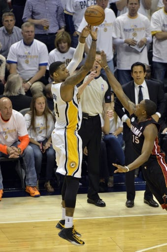 May 26, 2013; Indianapolis, IN, USA; Indiana Pacers small forward Paul George (24) shoots a three-point shot over Miami Heat point guard Mario Chalmers (15) during the third quarter in game three of the Eastern Conference finals of the 2013 NBA Playoffs at Bankers Life Fieldhouse. Miami defeated Indiana 114-96.  Mandatory Credit: Jamie Rhodes-USA TODAY Sports