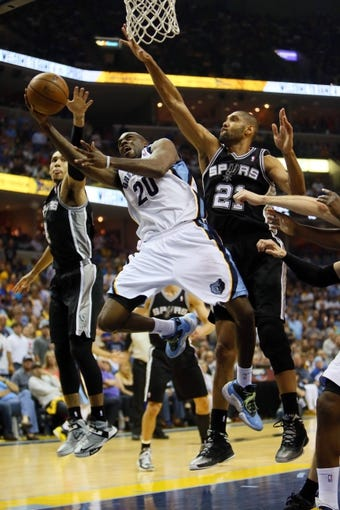 May 27, 2013; Memphis, TN, USA; Memphis Grizzlies small forward Quincy Pondexter (20) shoots between San Antonio Spurs shooting guard Danny Green (4) and power forward Tim Duncan (21) in the second half of game four of the Western Conference finals of the 2013 NBA Playoffs at FedEx Forum.  The Spurs won 93-86.  Mandatory Credit: Spruce Derden-USA TODAY Sports