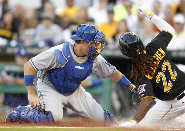 Jun 14, 2013; Pittsburgh, PA, USA; Los Angeles Dodgers catcher A.J. Ellis (left) tags out Pittsburgh Pirates center fielder Andrew McCutchen (22) at the plate during the third inning at PNC Park. Mandatory Credit: Charles LeClaire-USA TODAY Sports