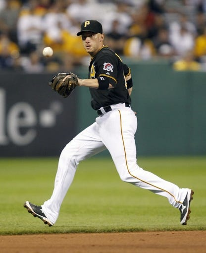 Jun 14, 2013; Pittsburgh, PA, USA; Pittsburgh Pirates shortstop Clint Barmes (12) tracks down a ground ball against the in the Los Angeles Dodgers during the ninth inning at PNC Park. The Pittsburgh Pirates won 3-0. Mandatory Credit: Charles LeClaire-USA TODAY Sports