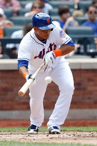 Jun 15, 2013; Flushing, NY,USA;  New York Mets center fielder Juan Lagares (12) bunts during the third inning against the Chicago Cubs at Citi Field.  Mandatory Credit: Anthony Gruppuso-USA TODAY Sports