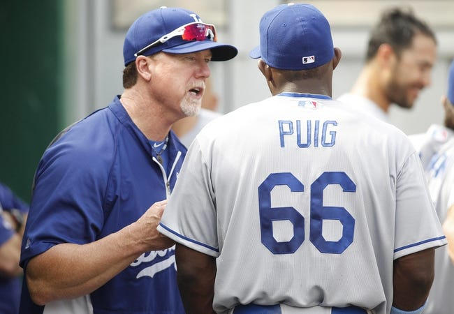 Jun 16, 2013; Pittsburgh, PA, USA; Los Angeles Dodgers batting coach Mark McGwire (12) talks to right fielder Yasiel Puig (66) in the dugout during the fifth inning against the Pittsburgh Pirates at PNC Park. The Pittsburgh Pirates won 6-3. Mandatory Credit: Charles LeClaire-USA TODAY Sports