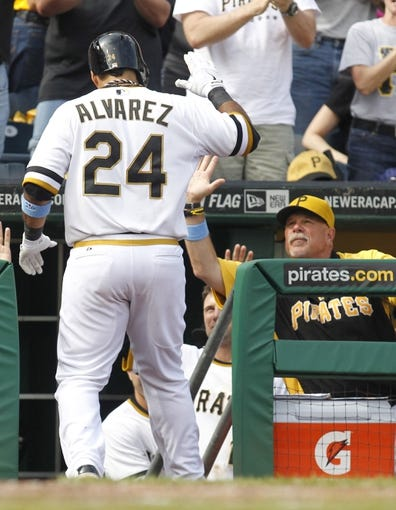 Jun 16, 2013; Pittsburgh, PA, USA; Pittsburgh Pirates third baseman Pedro Alvarez (24) is greeted by Pittsburgh Pirates pitching coach Ray Searage (right) after hitting a three run home run against the Los Angeles Dodgers during the fifth inning at PNC Park. The Pittsburgh Pirates won 6-3. Mandatory Credit: Charles LeClaire-USA TODAY Sports