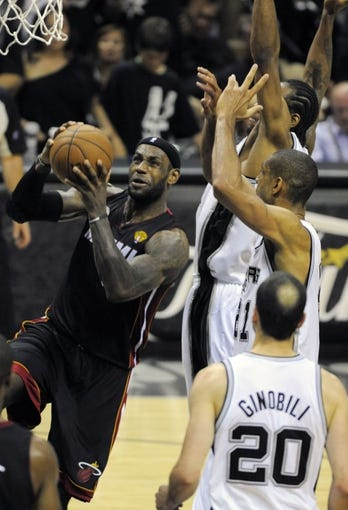 Jun 16, 2013; San Antonio, TX, USA; Miami Heat small forward LeBron James (6) drives past San Antonio Spurs power forward Tim Duncan (21) and Kawhi Leonard (2) during the fourth quarter of game five in the 2013 NBA Finals at the AT&T Center. Mandatory Credit: Brendan Maloney-USA TODAY Sports