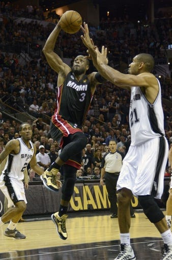 Jun 16, 2013; San Antonio, TX, USA;  Miami Heat shooting guard Dwyane Wade (3) lays the ball up past San Antonio Spurs power forward Tim Duncan (21) during the fourth quarter of game five in the 2013 NBA Finals at the AT&T Center. Mandatory Credit: Brendan Maloney-USA TODAY Sports