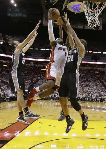 Jun 18, 2013; Miami, FL, USA; Miami Heat small forward LeBron James (6) drives to the basket between San Antonio Spurs shooting guard Manu Ginobili (20) and Tim Duncan (21) during the second half of game six in the 2013 NBA Finals at American Airlines Arena. Mandatory Credit: Lynne SladkyPool Photo-USA TODAY Sports