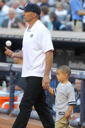 Jun 19, 2013; Bronx, NY, USA; Brooklyn Nets head coach Jason Kidd and his son Chance walk out for the ceremonial first pitch before the start of a game between the New York Yankees and the Los Angeles Dodgers at Yankee Stadium. Mandatory Credit: Brad Penner-USA TODAY Sports
