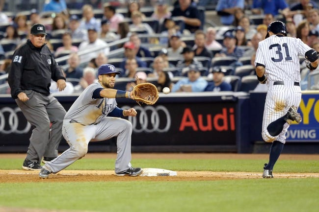 Jun 21, 2013; Bronx, NY, USA;  Tampa Bay Rays first baseman James Loney (21) forces out New York Yankees right fielder Ichiro Suzuki (31) during the fifth inning at Yankee Stadium.  Mandatory Credit: Anthony Gruppuso-USA TODAY Sports