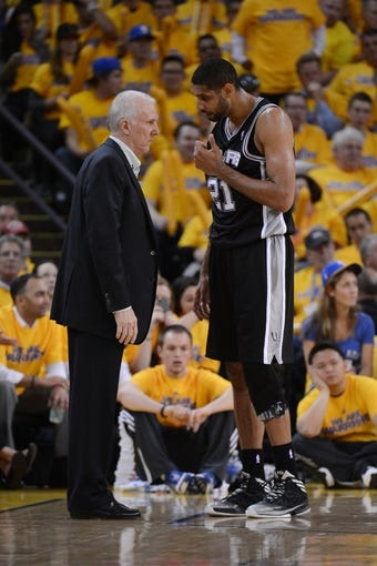May 16, 2013; Oakland, CA, USA; San Antonio Spurs head coach Gregg Popovich (left) instructs power forward Tim Duncan (21) during the third quarter in game six of the second round of the 2013 NBA Playoffs against the Golden State Warriors at Oracle Arena. The Spurs defeated the Warriors 94-82.  Mandatory Credit: Kyle Terada-USA TODAY Sports