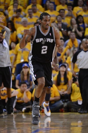 May 16, 2013; Oakland, CA, USA; San Antonio Spurs small forward Kawhi Leonard (2) celebrates after a play during the fourth quarter in game six of the second round of the 2013 NBA Playoffs against the Golden State Warriors at Oracle Arena. The Spurs defeated the Warriors 94-82.  Mandatory Credit: Kyle Terada-USA TODAY Sports