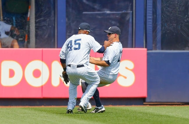 Jun 22, 2013; Bronx, NY, USA; New York Yankees left fielder Zoilo Almonte (45) and center fielder Brett Gardner (11) misplay a ball during the sixth inning against the Tampa Bay Rays  at Yankee Stadium.  Mandatory Credit: Anthony Gruppuso-USA TODAY Sports