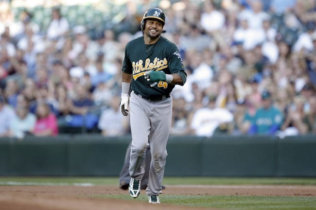 Jun 22, 2013; Seattle, WA, USA; Oakland Athletics designated hitter Coco Crisp (4) smiles as he jogs back to the dugout after being caught stealing against the Seattle mariners during the first inning at Safeco Field. Mandatory Credit: Joe Nicholson-USA TODAY Sports