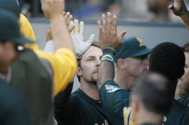 Jun 22, 2013; Seattle, WA, USA; Oakland Athletics shortstop Jed Lowrie (8) is greeted in the dugout after hitting an RBI-sacrifice fly against the Seattle Mariners during the third inning at Safeco Field. Mandatory Credit: Joe Nicholson-USA TODAY Sports
