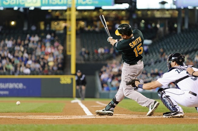 Jun 23, 2013; Seattle, WA, USA; Oakland Athletics designated hitter Seth Smith (15) hits a ground ball single against the Seattle Mariners during the 1st inning at Safeco Field. Mandatory Credit: Steven Bisig-USA TODAY Sports