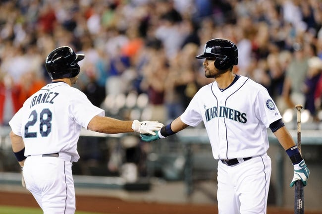 Jun 23, 2013; Seattle, WA, USA; Seattle Mariners designated hitter Raul Ibanez (28) and Seattle Mariners center fielder Franklin Gutierrez (21) high five after Ibanez hit a 2-run home run against the Oakland Athletics during the 1st inning at Safeco Field. Mandatory Credit: Steven Bisig-USA TODAY Sports