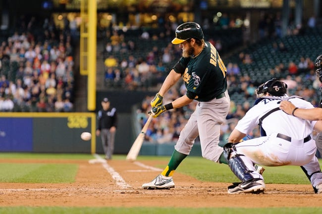 Jun 23, 2013; Seattle, WA, USA; Oakland Athletics right fielder Josh Reddick (16) hits a sacrifice RBI ground ball during the 6th inning against the Seattle Mariners at Safeco Field. Mandatory Credit: Steven Bisig-USA TODAY Sports