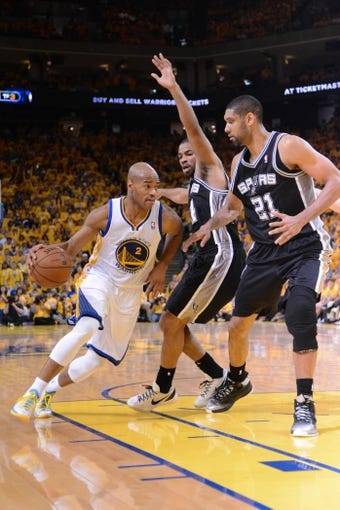 May 12, 2013; Oakland, CA, USA; Golden State Warriors point guard Jarrett Jack (2) dribbles against San Antonio Spurs point guard Gary Neal (14, center) and power forward Tim Duncan (21) during the fourth quarter in game four of the second round of the 2013 NBA Playoffs at Oracle Arena. The Warriors defeated the Spurs 97-87 in overtime. Mandatory Credit: Kyle Terada-USA TODAY Sports