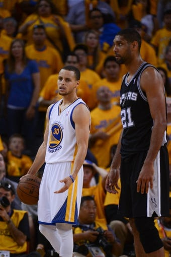 May 12, 2013; Oakland, CA, USA; Golden State Warriors point guard Stephen Curry (30) reacts as San Antonio Spurs power forward Tim Duncan (21) looks on during overtime in game four of the second round of the 2013 NBA Playoffs at Oracle Arena. The Warriors defeated the Spurs 97-87 in overtime. Mandatory Credit: Kyle Terada-USA TODAY Sports