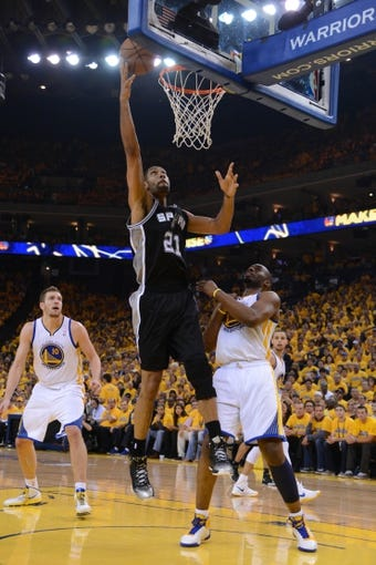 May 10, 2013; Oakland, CA, USA; San Antonio Spurs power forward Tim Duncan (21) shoots the ball against Golden State Warriors power forward Carl Landry (7, right) during the second quarter in game three of the second round of the 2013 NBA Playoffs at Oracle Arena. The Spurs defeated the Warriors 102-92. Mandatory Credit: Kyle Terada-USA TODAY Sports