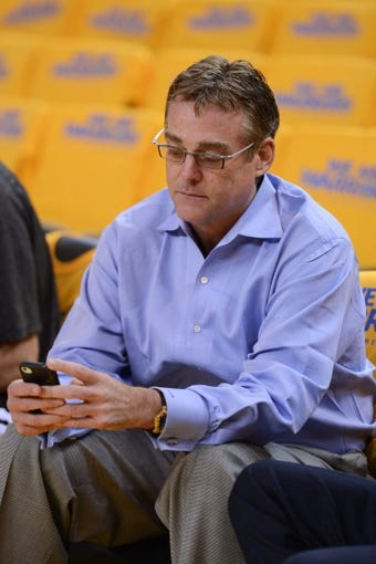 May 10, 2013; Oakland, CA, USA; San Antonio Spurs president of sports franchises R.C. Buford looks at his cell phone before game three of the second round of the 2013 NBA Playoffs against the Golden State Warriors at Oracle Arena. The Spurs defeated the Warriors 102-92. Mandatory Credit: Kyle Terada-USA TODAY Sports