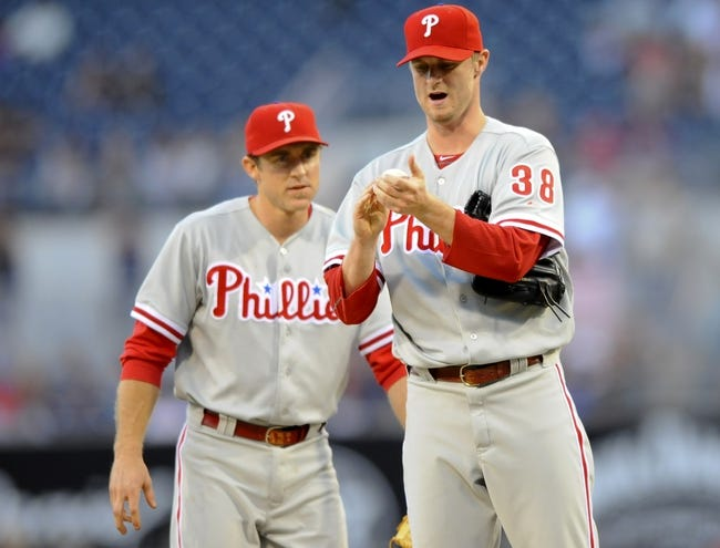 June 25, 2013; San Diego, CA, USA; Philadelphia Phillies second baseman Chase Utley (left) talks with starting pitcher Kyle Kendrick (38) after a double during the second inning against the San Diego Padres at Petco Park. Mandatory Credit: Christopher Hanewinckel-USA TODAY Sports