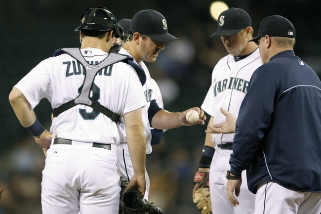 Jun 25, 2013; Seattle, WA, USA; Seattle Mariners pitcher Joe Saunders (23) is relieved by manager Eric Wedge (22) during the second inning against the Pittsburgh Pirates at Safeco Field. Mandatory Credit: Joe Nicholson-USA TODAY Sports