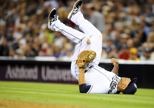 June 25, 2013; San Diego, CA, USA; San Diego Padres first baseman Kyle Blanks (88) falls over after losing control of the ball on a hit by Philadelphia Phillies second baseman Chase Utley (not pictured) during the sixth inning at Petco Park.  Mandatory Credit: Christopher Hanewinckel-USA TODAY Sports