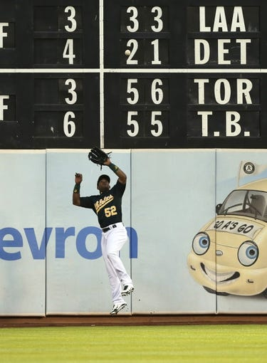 Jun 25, 2013; Oakland, CA, USA; Oakland Athletics left fielder Yoenis Cespedes (52) makes the catch along the wall against the Cincinnati Reds during the fifth inning at O.co Coliseum. The Oakland Athletics defeated the Cincinnati Reds 7-3. Mandatory Credit: Kelley L Cox-USA TODAY Sports