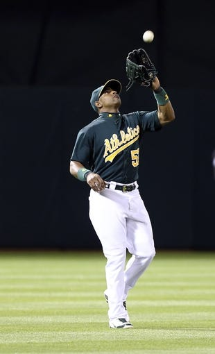 Jun 25, 2013; Oakland, CA, USA; Oakland Athletics left fielder Yoenis Cespedes (52) catches the ball against the Cincinnati Reds during the sixth inning at O.co Coliseum. The Oakland Athletics defeated the Cincinnati Reds 7-3. Mandatory Credit: Kelley L Cox-USA TODAY Sports