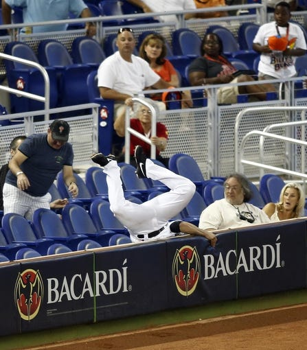 Jun 26, 2013; Miami, FL, USA;  Miami Marlins third baseman Placido Polanco (30) dives into the stands but cannot catch a foul ball hit by Minnesota Twins center fielder Clete Thomas (not pictured) in the second inning at Marlins Park.  Mandatory Credit: Robert Mayer-USA TODAY Sports