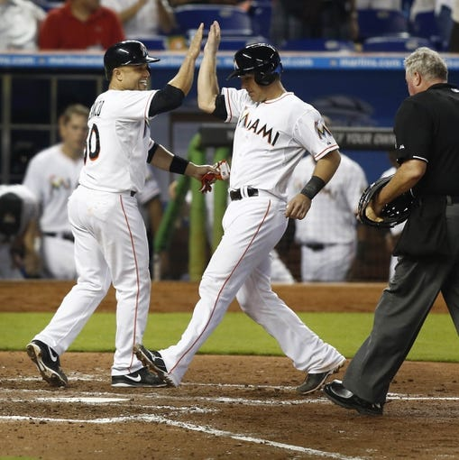 Jun 26, 2013; Miami, FL, USA;  Miami Marlins third baseman Placido Polanco (30) congratulates catcher Jeff Mathis (6) on his two run home run home run in the fifth inning at Marlins Park. The Marlins won 5-3. Mandatory Credit: Robert Mayer-USA TODAY Sports