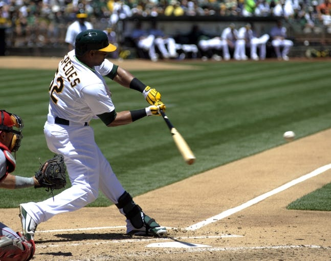 Jun 26, 2013; Oakland, CA, USA; Oakland Athletics left fielder Yoenis Cespedes (52) hits a single during the fourth inning of the game against the Cincinnati Reds at O.Co Coliseum. Mandatory Credit: Ed Szczepanski-USA TODAY Sports