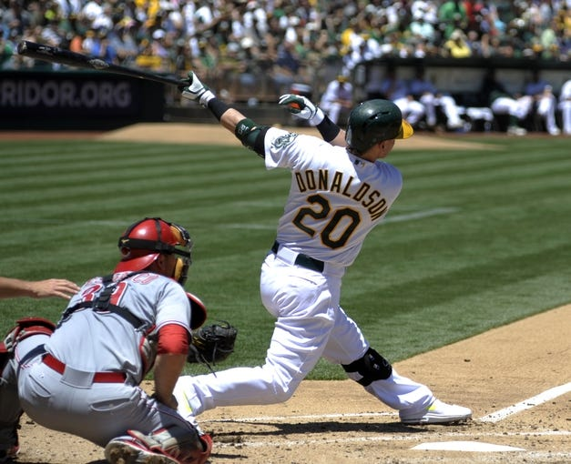 Jun 26, 2013; Oakland, CA, USA; Oakland Athletics third baseman Josh Donaldson (20) hits a home run against the Cincinnati Reds during the fourth inning at O.Co Coliseum. Mandatory Credit: Ed Szczepanski-USA TODAY Sports
