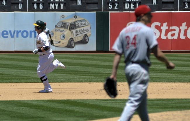 Jun 26, 2013; Oakland, CA, USA; Oakland Athletics third baseman Josh Donaldson (20) rounds the bases after hitting a home run off of Cincinnati Reds starting pitcher Homer Bailey (34, right) during the fourth inning at O.Co Coliseum. Mandatory Credit: Ed Szczepanski-USA TODAY Sports