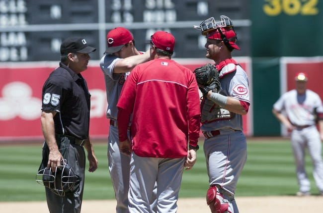 Jun 26, 2013; Oakland, CA, USA; Cincinnati Reds assistant pitching coach Mack Jenkins (57) and starting pitcher Homer Bailey (34) and catcher Devin Mesoraco (39) meet at the mound during the fourth inning of the game against the Oakland Athletics at O.Co Coliseum. Mandatory Credit: Ed Szczepanski-USA TODAY Sports