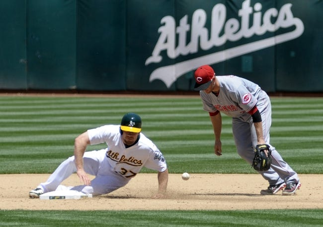 Jun 26, 2013; Oakland, CA, USA; Oakland Athletics first baseman Brandon Moss (37) slides into second base as Cincinnati Reds shortstop Cesar Izturis (3) is unable to turn the double play during the sixth inning at O.Co Coliseum. The Oakland Athletics defeated the Cincinnati Reds 5-0. Mandatory Credit: Ed Szczepanski-USA TODAY Sports