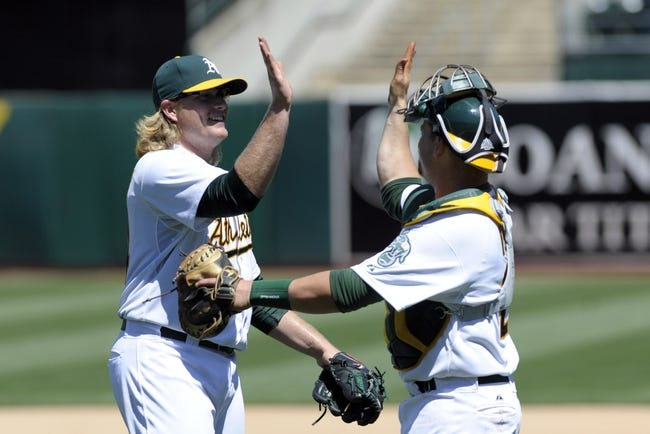 Jun 26, 2013; Oakland, CA, USA; Oakland Athletics starting pitcher A.J. Griffin (64) high fives catcher Stephen Vogt (21) after defeating the Cincinnati Reds at O.Co Coliseum. The Oakland Athletics defeated the Cincinnati Reds 5-0. Mandatory Credit: Ed Szczepanski-USA TODAY Sports